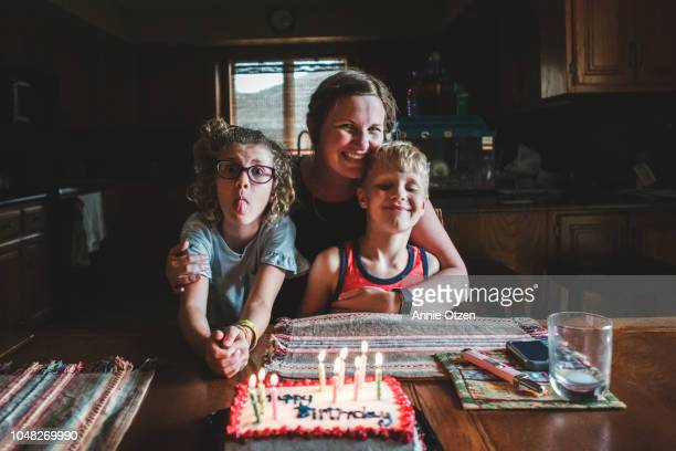 mother and children sitting by a birthday cake - birthday candle stock pictures, royalty-free photos & images