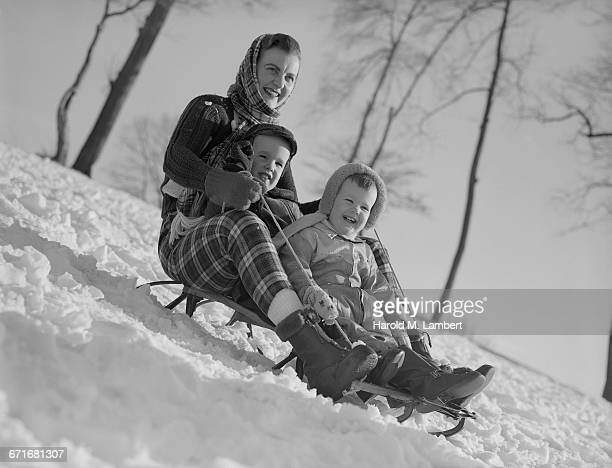 mother and children sitting on sledge - neckwear stock pictures, royalty-free photos & images