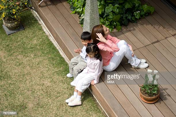 Mother and children sitting on wooden deck