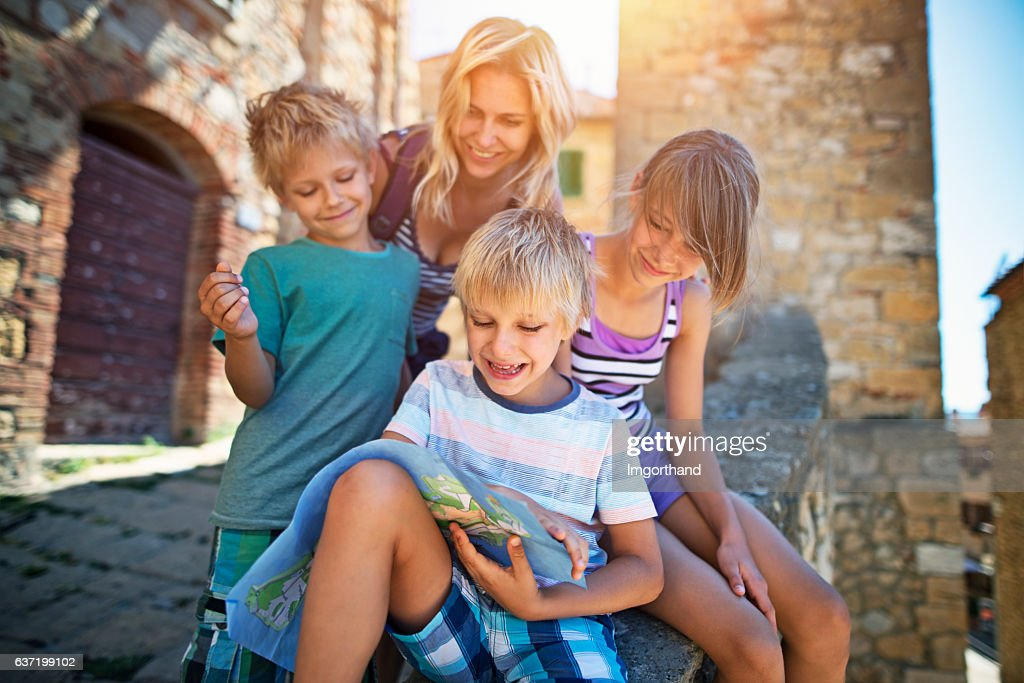 Mother and children tourist checking map in an Italian town : Stock Photo