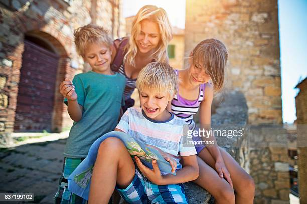 Mother and children tourist checking map in an Italian town