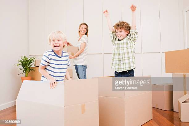 Mother and children unpacking boxes in new house