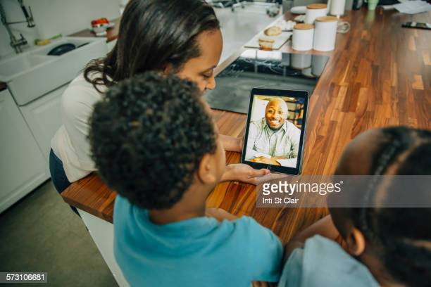 Mother and children video chatting with father in kitchen