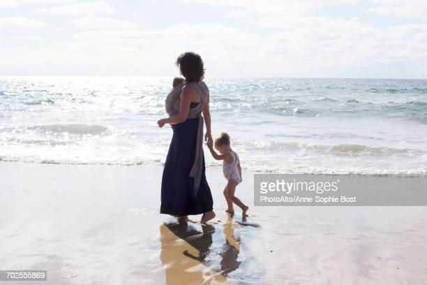 mother and children walking on beach - anne sophie mutter stock-fotos und bilder