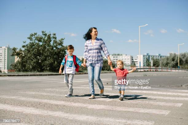 Mother And Children Walking On Zebra Crossing