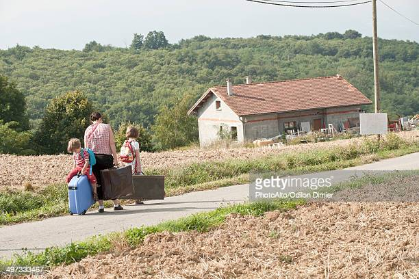 mother and children wandering through countryside, dragging suitcases behind them - emigration and immigration stock pictures, royalty-free photos & images
