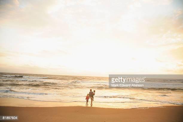 mother and children watching sunset - schrägansicht stock-fotos und bilder