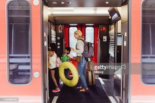 mother and children with luggage walking in train at station - vehicle door stock pictures, royalty-free photos & images