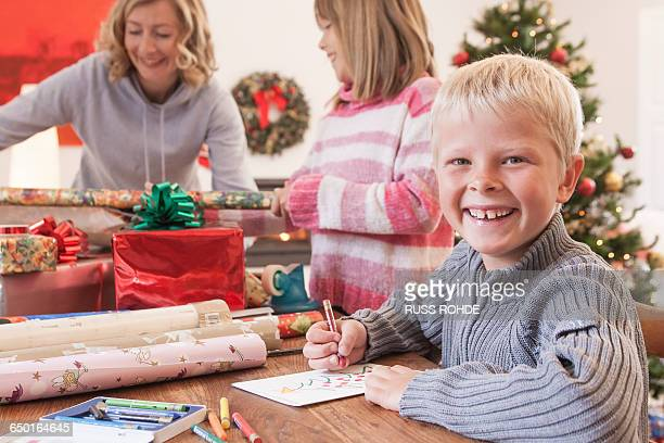 Mother and children wrapping christmas gifts
