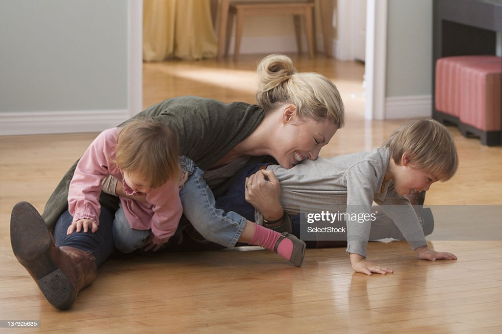 Mother and children wrestling : Stock Photo