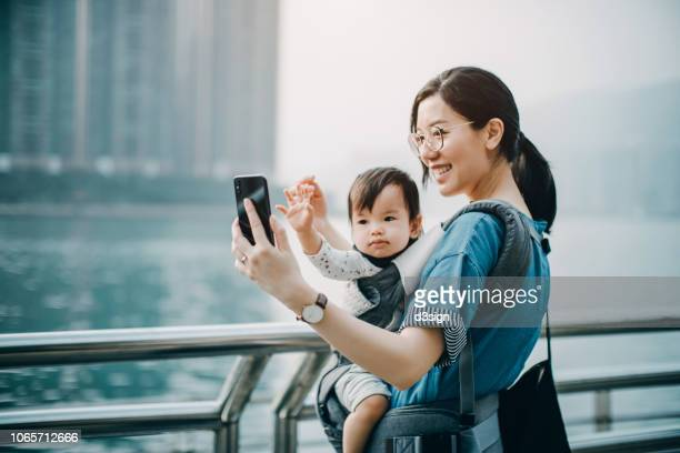 mother and cute baby girl taking selfie joyfully with smartphone by the harbour in city - waving gesture stock photos and pictures