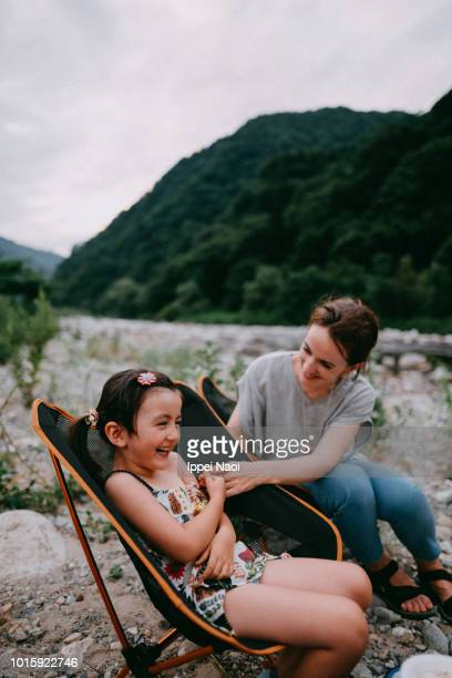 Mother and cute little girl having fun time at campsite by river, Japan