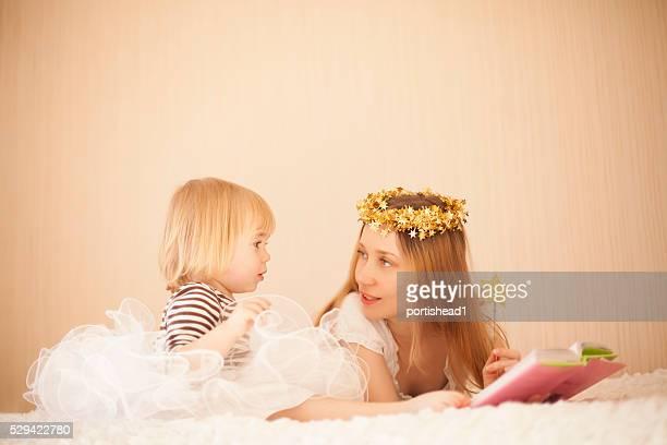 Lindo madre y la niña pequeña lectura en la cama