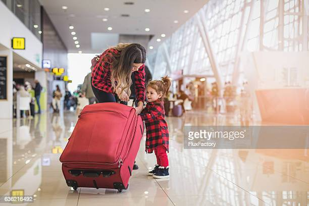 mother and cute toddler girl pulling together a suitcase - checked pattern stock pictures, royalty-free photos & images
