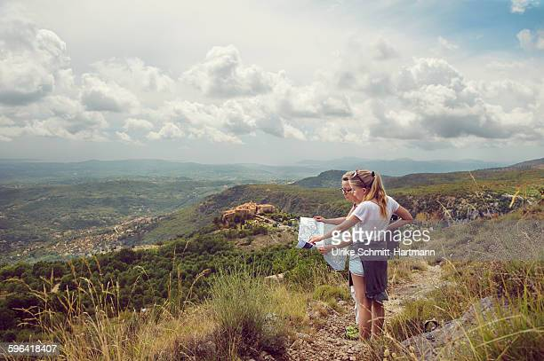 Mother and daugher looking at map in mountains