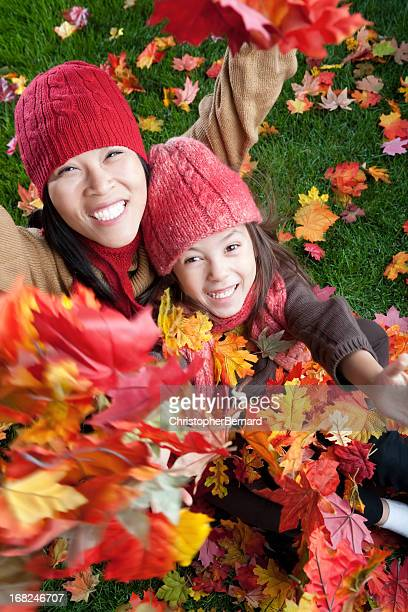 Mother and daugher throwing autumn leaves