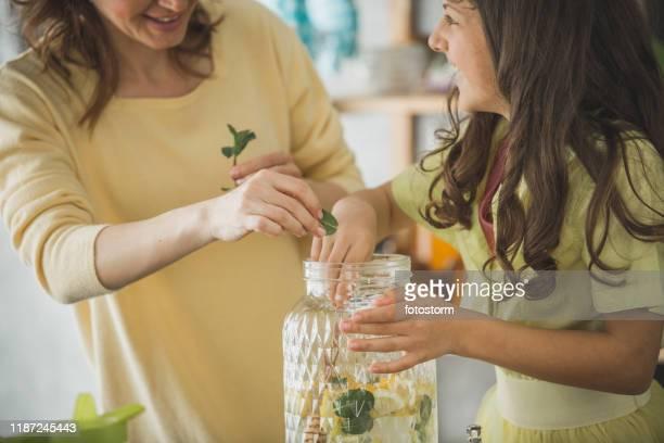 madre e hija añadiendo menta en limonada - mint plant family fotografías e imágenes de stock