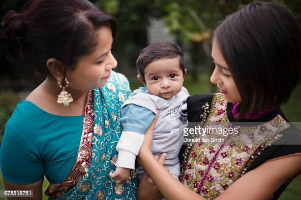 Mother and daughter admiring baby boy