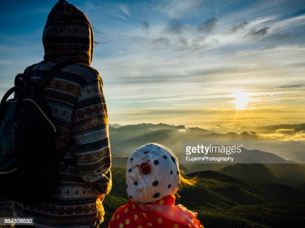 Mother and daughter admiring sunrise on the top of a mountain