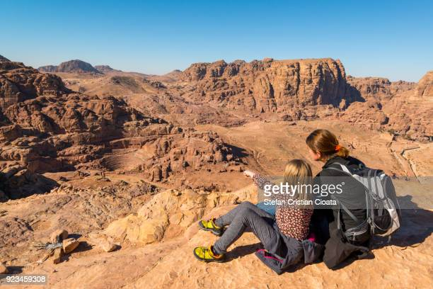 mother and daughter admiring the roman amphitheatre in petra - history stock pictures, royalty-free photos & images