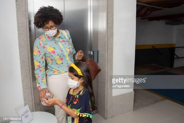 エレベーターの中の母と娘のアルクールゲル - alcool gel ストックフォトと画像