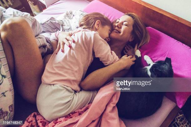 mother and daughter and cat sleeping together - ivanjekic stock pictures, royalty-free photos & images