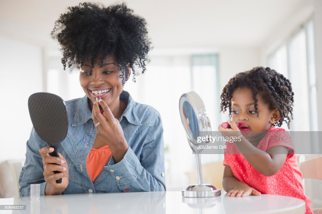 Mother and daughter applying makeup : Stock Photo