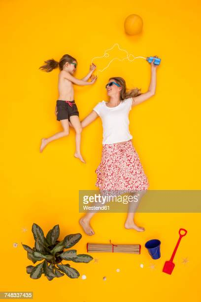 Mother and daughter applying suncream at the beach