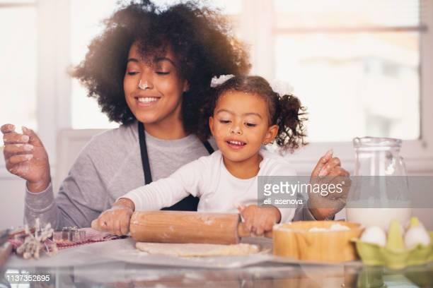 madre e hija están horneando juntos - black cook fotografías e imágenes de stock