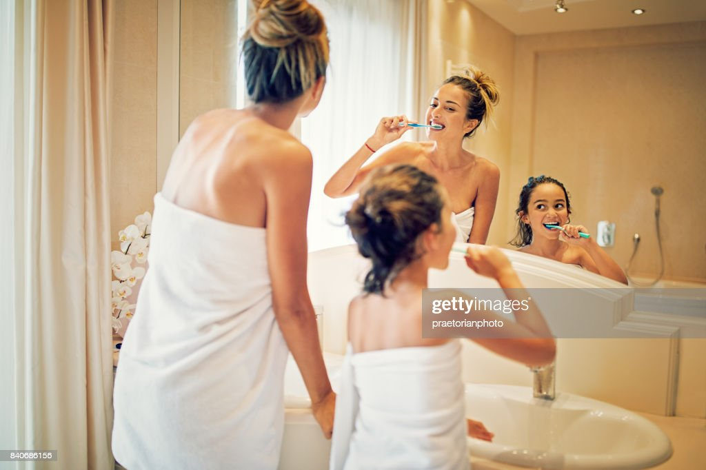 Mother and daughter are brushing their teeth in the bathroom : Stock Photo