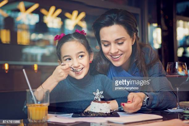 Mother and daughter are eating a cake in the cafe