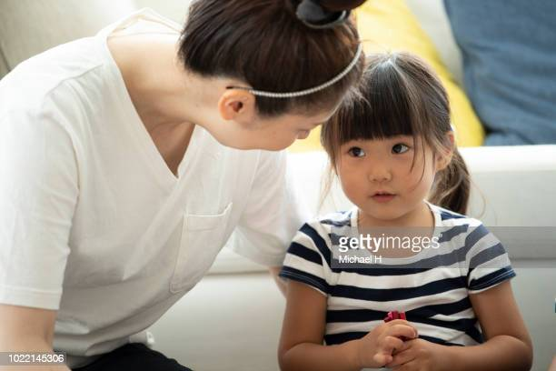mother and daughter are looking at each other - nur japaner stock-fotos und bilder