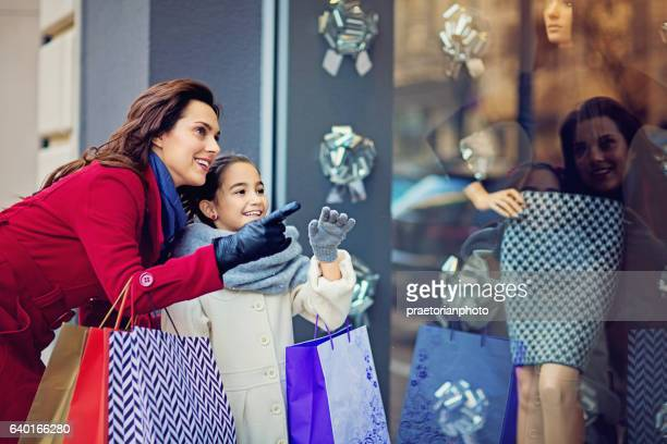 Mother and daughter are looking shop window