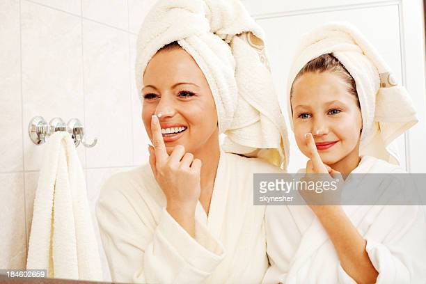 Mother and daughter are putting on face cream.