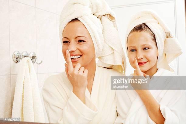 Mère et fille se mettre de la crème sur le visage.