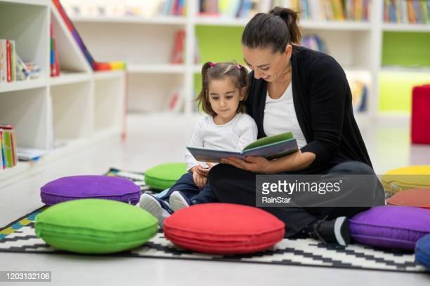 mother and daughter are reading books in the nursery - geographical locations stock pictures, royalty-free photos & images
