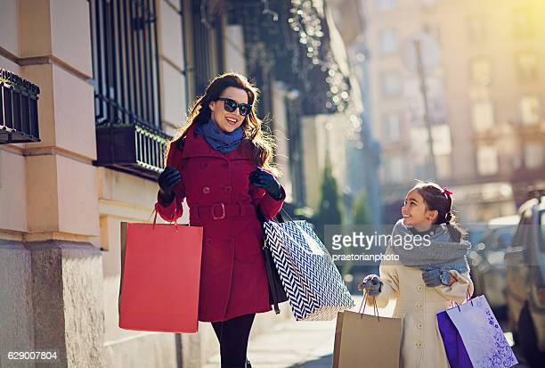 mother and daughter are walking on the street - luxury girl stock photos and pictures