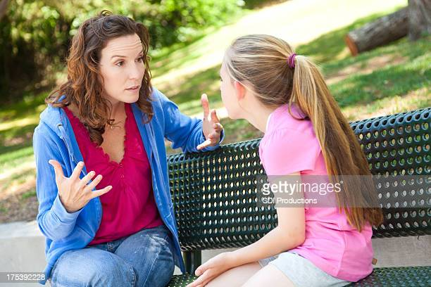 Mother and daughter arguing on a park bench