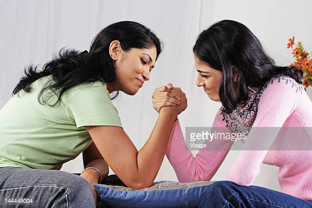 Mother and daughter arm wrestling