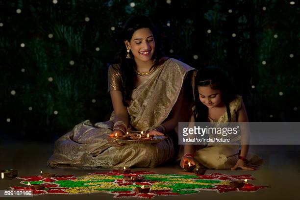 Mother and daughter arranging diyas