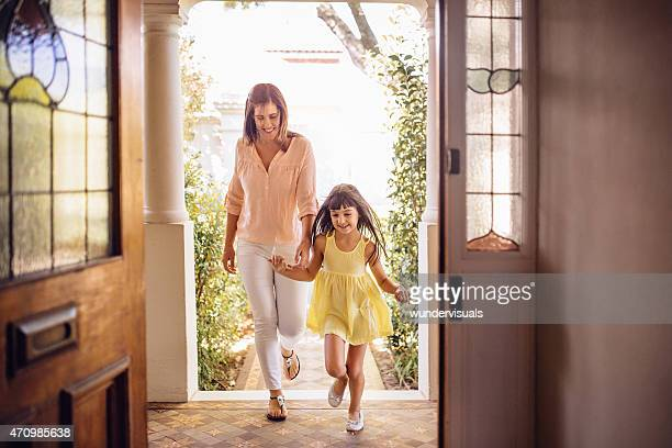 Mother and daughter arriving home through their front door