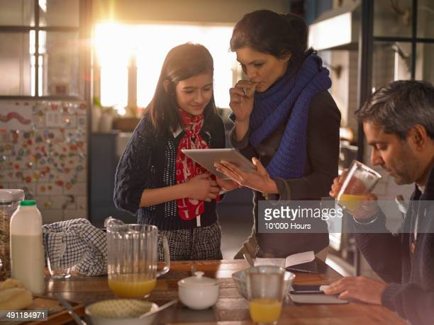 Mother and daughter at breakfast looking at ipad