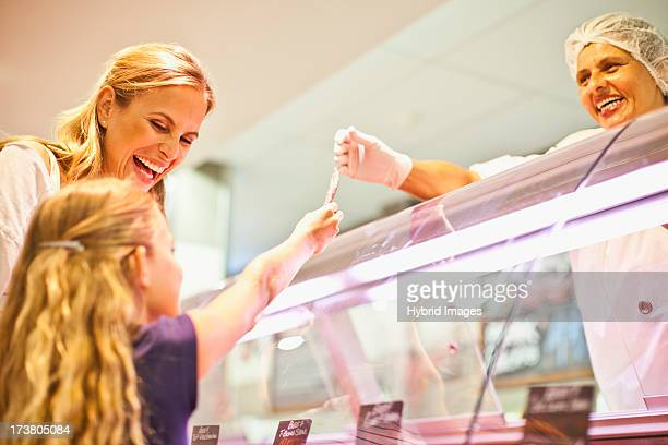 Mother and daughter at butcher counter