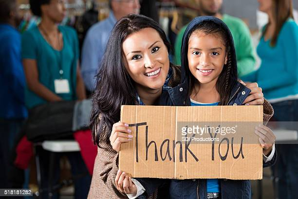 mother and daughter at coat drive - charitable donation stock pictures, royalty-free photos & images