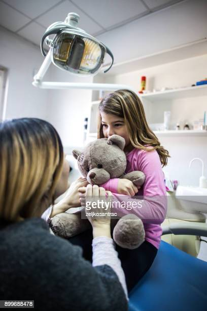 mother and daughter at dental clinic - pediatric dentistry stock photos and pictures
