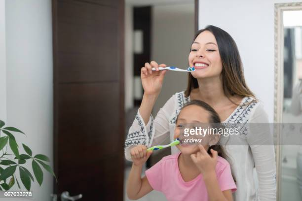 Mother and daughter at home brushing their teeth