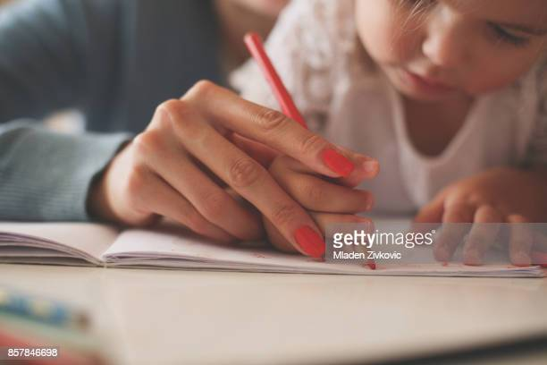 mother and daughter at home. mother teaching her daughter to drawing and writing. - drawing art product stock pictures, royalty-free photos & images