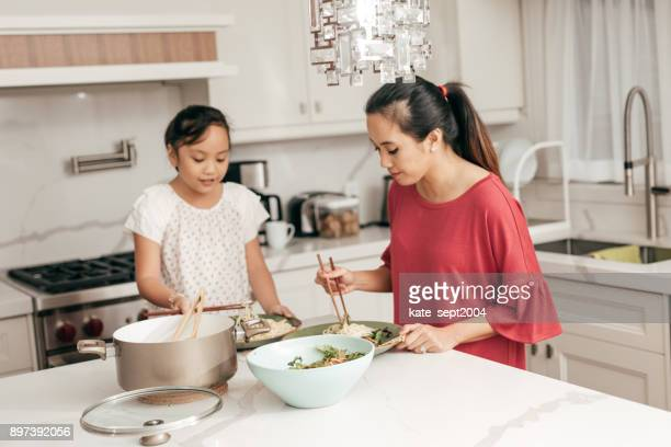 mother and daughter at home - filipino family dinner stock pictures, royalty-free photos & images