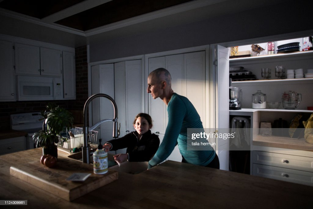 mother and daughter at kitchen sink : Stock-Foto