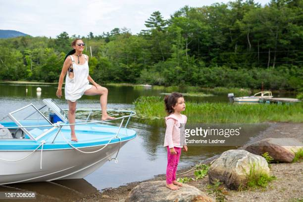 mother and daughter at lake's edge with vintage motorboat in maine - catherine ledner stock pictures, royalty-free photos & images